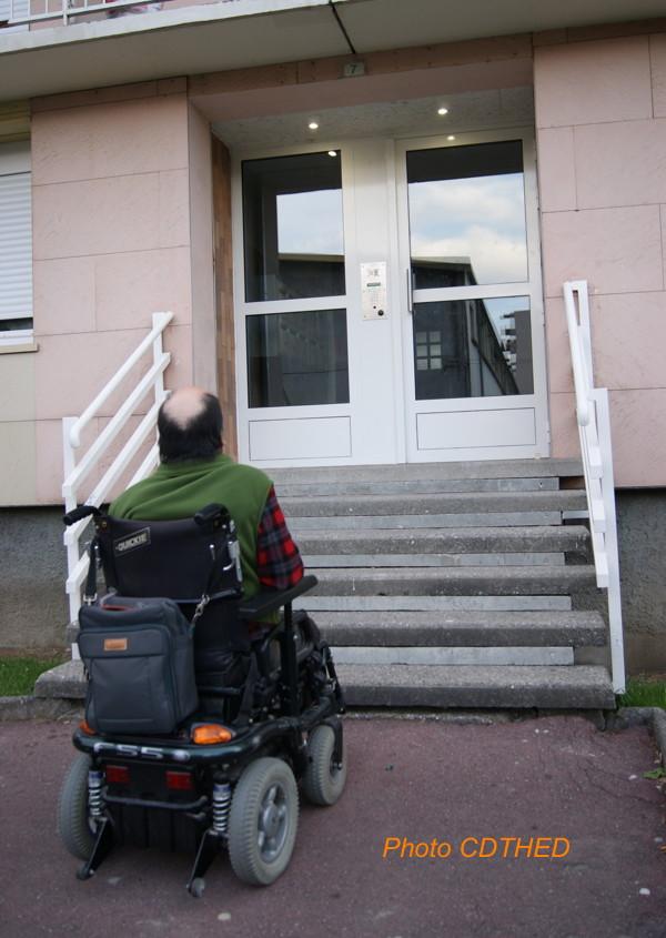 Sur la photo couleur, on voit de dos une personne handicapée en fauteuil roulant électrique. Devant elle, un escalier de six marches qui mène à une entrée d'immeuble... Inaccessible donc !